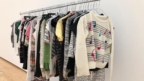 """Kleidungsstücke mit aufgedruckten Noten hängen an einem Kleiderständer. """"Pret-a-porter"""" von Christian Marclay"""