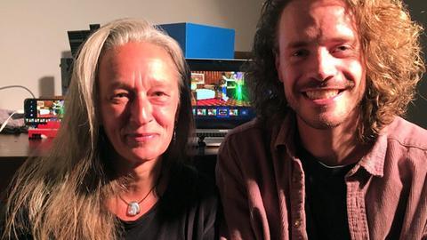 Silja Melch und Dominik Reh: Weißhaarige Frau und Mann mit halblangen, lockigen Haaren, beide lachen.