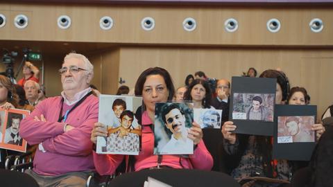 Angehörige zeigen Fotos von Opfern
