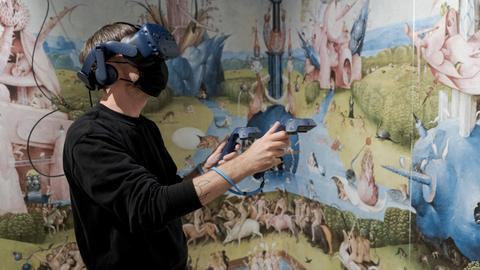 """Mann mit VR Brille vor Hironimus Boschs """"Garten der Lüste"""""""