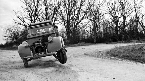 """Selfies hat Régis Bossu nie von sich gemacht – bis auf dieses: 1966 fotografiert er sich in seinem ersten Auto, einer """"Ente"""", mit Selbstauslöser. Was aussieht, wie ein rasantes Fahrmanöver ist ein """"Fake"""": Unter den rechten Vorderreifen hatte er einen Wagenheber geklemmt."""