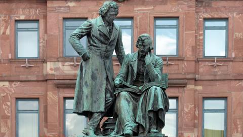 Das Brüder-Grimm-Denkmal von 1896 mit Wilhelm Grimm sitzend und Jacob Grimm stehend, aufgenommen am 02.09.2015 vor dem historischen Rathaus auf dem Marktplatz in Hanau