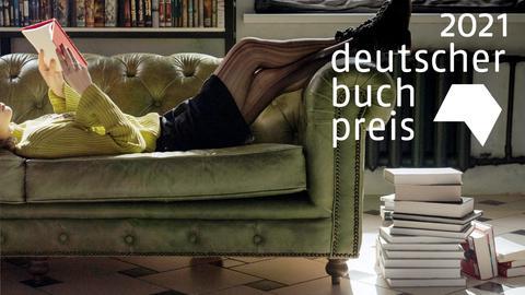 Eine Szene in einem Wohnzimmer: eine Frau liegt auf einem alten Sofa und liest ein Buch. Daneben ein Stapel Bücher auf dem Boden.