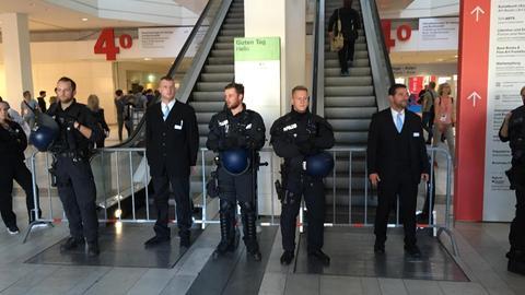 Polizisten stehen vor Rolltreppe auf der Buchmesse