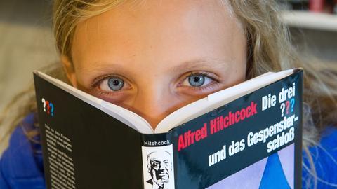 """Mädchen schaut über ein """"Die drei Fragezeichen""""-Buch hinweg"""