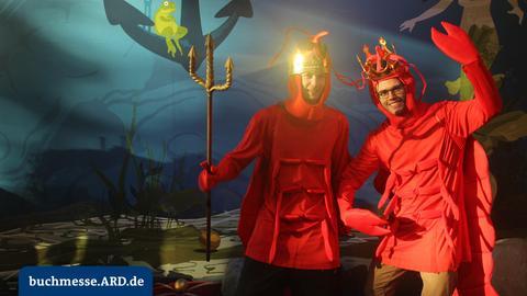 Kostümierte Person(en) posieren vor Unterwasser-Hintergrund in einer Fotobox