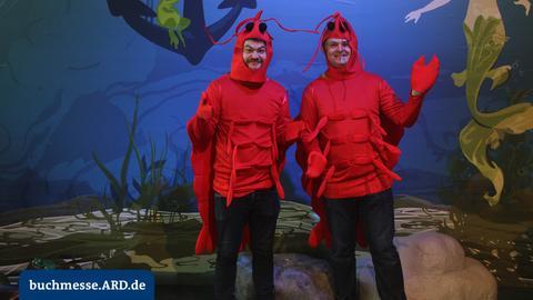 Kostümierte Personen vor Unterwasserhintergrund