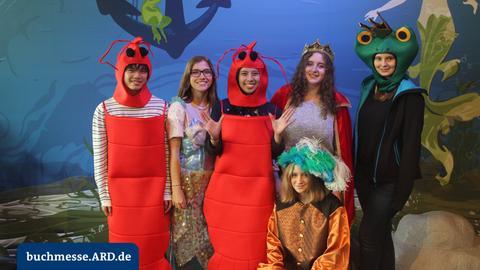 Kostümierte Personen vor Unterwasserhintergrund in einer Fotobox