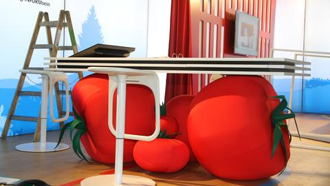 Sitzkissen, die aussehen wie Tomaten, liegen unter einem Tisch