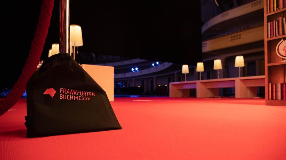 Eine Tasche mit Aufschrift Frankfurter Buchmesse steht auf einem roten Teppich.