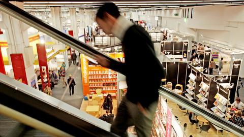Eine Person fährt auf einer Rolltreppe hoch - sie ist nur verschwommen zu sehen - dahinter Blick auf eine Messehalle, in der nur wenige Menschen unterwegs sind.