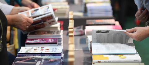 Menschen auf der Buchmesse blättern in Büchern