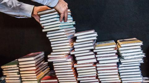 Ein Mann sortiert auf der Buchmesse stapelweise Bücher.