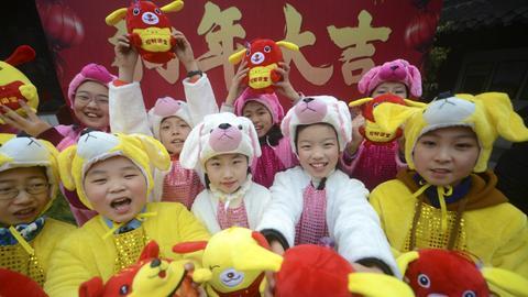 Chinesische Kinder feiern das Neujahrsfest verkleidet