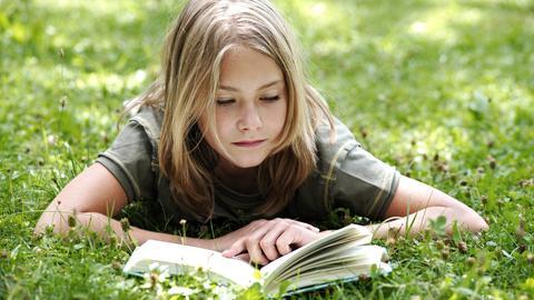 Ein lesendes Mädchen liegt bäuchlings im Gras.