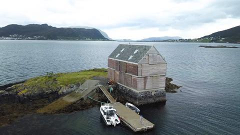 Weekend House Straume, Knut Heltjnes Architects, ein Holzhaus auf einer Landzunge mit Boot am Bootsanleger