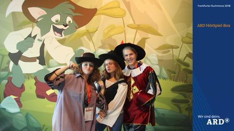 Verkleidete Besucher der Buchmesse vor einem märchenhaften Hintergrund mit gestiefeltem Kater.