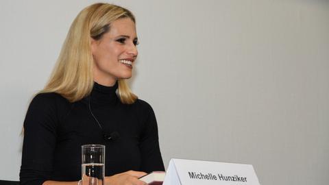 Michelle Hunziker sitzt lächelnd an einem Tisch auf auf einer Pressekonferenz.