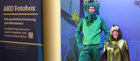 Zwei kostümierte Personen lassen sich vor Unterwasserkulisse fotografieren.