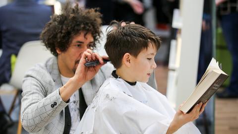 Friseur Danny Beuerbach schneidet einem Jungen die Haare, der Bub liest ein Buch vor.