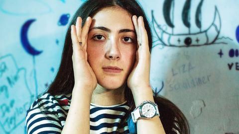 Fotografie eine jungen Frau, die die Hände an Seite ihres Gesichts hält.