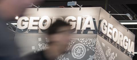 """Eine Frau läuft vor einem Stand mit """"Georgia""""-Schriftzug vorbei."""