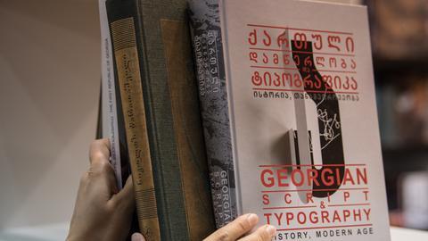 Hände, die Bücher mit georgischer Schrift in ein Regal stellen.