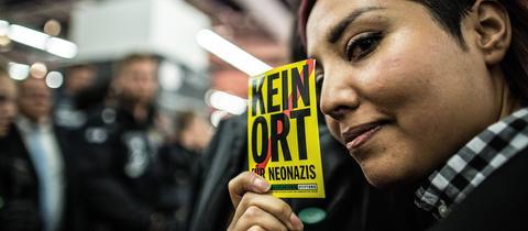 """Protest gegen Rechte bei der Buchmesse 2017 - eine Frau hält einen Aufkleber """"Kein Ort für Neonazis"""" hoch."""