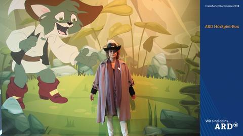 Verkleidete Besucher der Buchmesse vor einem märchenhaften Hintergrund mit gestiefeltem Kater