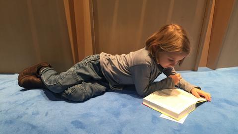 Siebenjähriger Junge lesend auf dem Boden
