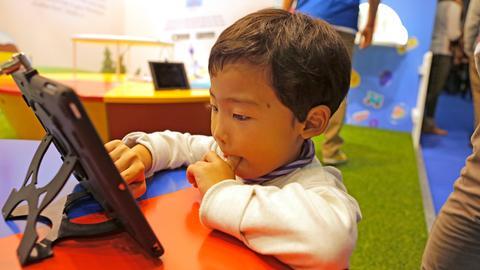 Ein Junge sitzt vor einem Tablet und tippt darauf.