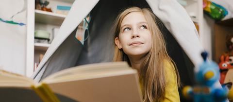 Ein Kind sitzt im Zelt und liest verträumt ein Buch