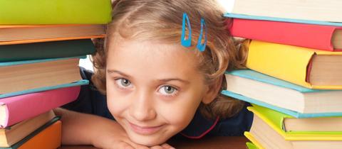 Ein Mädchen, das zwischen zwei Bücherstapeln hervorschaut.