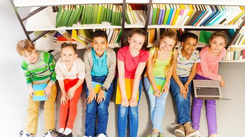 Kinder sitzen mit Büchern auf den Knien vor einem Bücherregal.