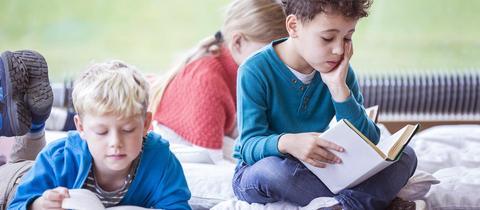 Kinder sitzen auf einem Teppich und lesen