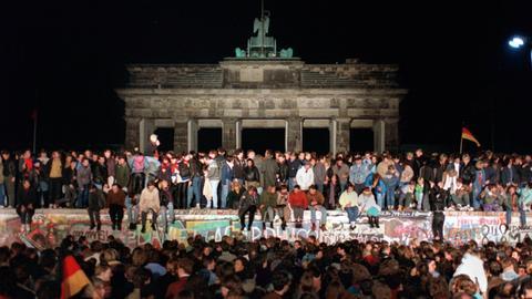 Mauerfall Jubelnde Menschen auf der Berliner Mauer am Brandenburger Tor am 10.11.1989