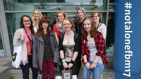 Acht junge Frauen stehen für ein Foto in einer Gruppe zusammen.