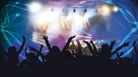 Menschen jubeln auf einem Konzert.