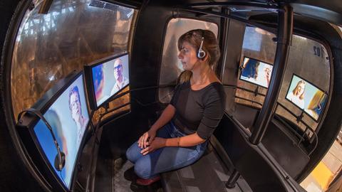 Mit einem Kopfhörer verfolgt eine Frau im Pavillon des Gastlandes Frankreich eine audiovisuelle Installation.