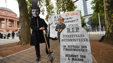 Zwei Attac-Aktivisten demonstrieren vor der Frankfurter Messe