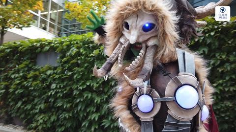 Cosplayerin verkleidet als - wir wissen es nicht - das haarige Ding hat Stoßzähne und ein Geweih sowie leuchtende Augen.