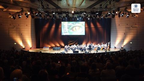Tolkien-Nachmittag auf der Frankfurter Buchmesse im vollbesetzten Saal Harmonie, auf der Bühne ein Orchester