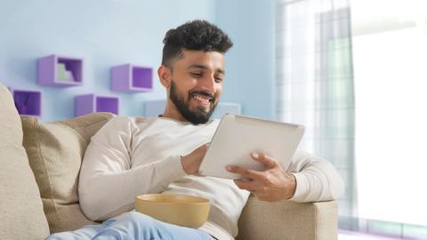 Ein Mann sitzt mit einem Tablet auf dem Sofa