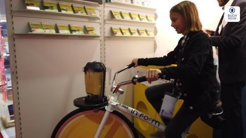 Ein Mädchen auf dem Smoothie-Fahrrad auf der Frankfurter Buchmesse