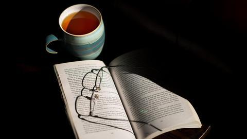 Eine Brille liegt auf einem aufgeschlagenen Buch, dahinter eine Tasse Tee.