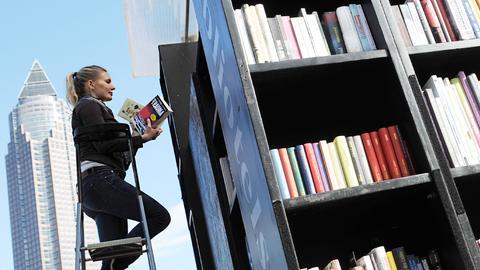 Eine Frau steht auf einer Leiter ubd stellt Bücher in die überdimensionierten Regale einer Freiluftbibliothek.