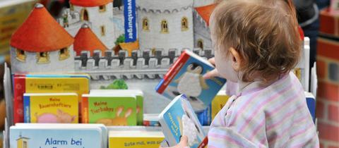 Kind räumt Bücher in einen Bücherständer
