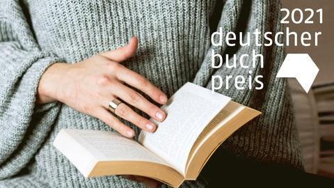 Eine Frau blättert in einem Buch - man sieht nur ihre Hände. Logo von Deutscher Buchpreis 2021