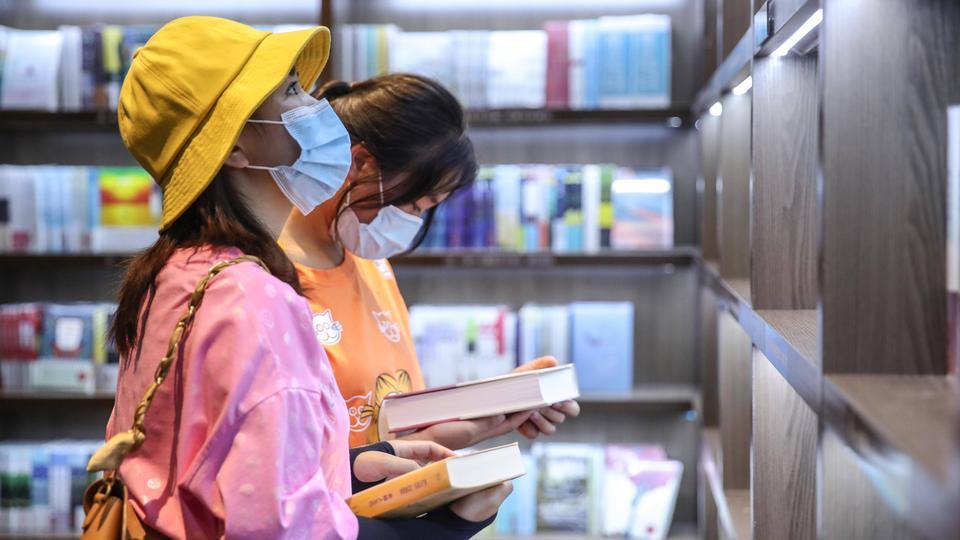 Zwei Frauen stöbern in einem Bücherrregal - sie tragen eine Mund-Nase-Bedeckung