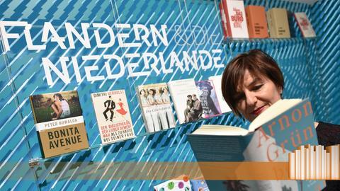 Eine Frau liest ein Buch von Arnon Grünberg vor dem Schriftzug Flandern und die Niederlande.